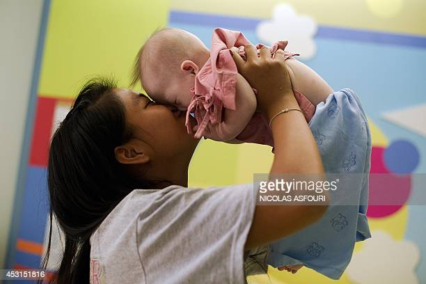 Thai surrogate mother Pattaramon Chanbua kiss her baby Gammy born with Down Syndrome at the Samitivej hospital Sriracha district in Chonburi province...