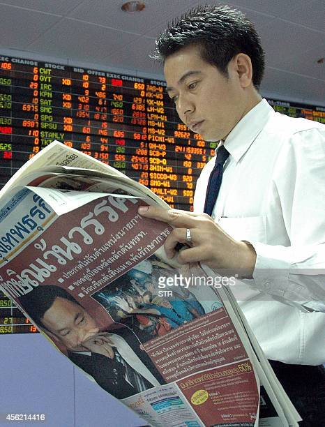 A Thai trader walks past an electronic screen displaying rise in market shares at a securities house while reading newspaper in Bangkok 05 April 2006...