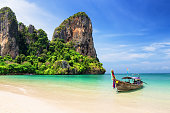 Thai traditional wooden longtail boat and beautiful sand beach
