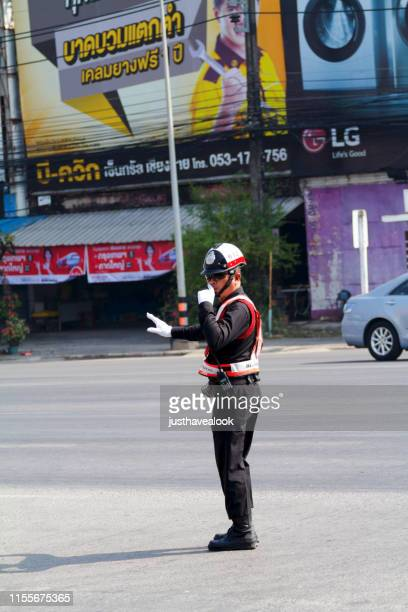 thai traffic cop with whistle on street - traffic cop stock pictures, royalty-free photos & images