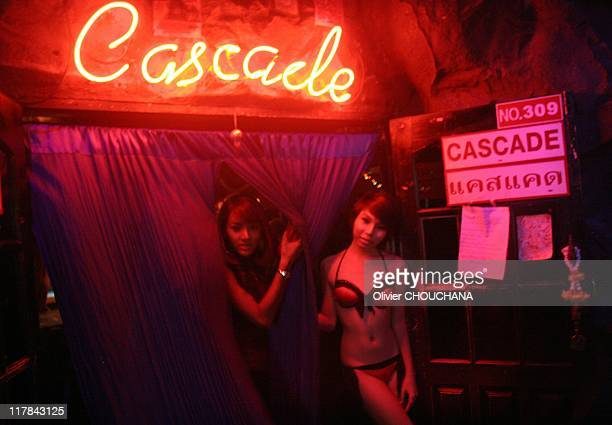 Thai transexual prostitutes greet customers at the entrance of a gogo bar where taking photos is strictly prohibited in the street of Soi Nana on...