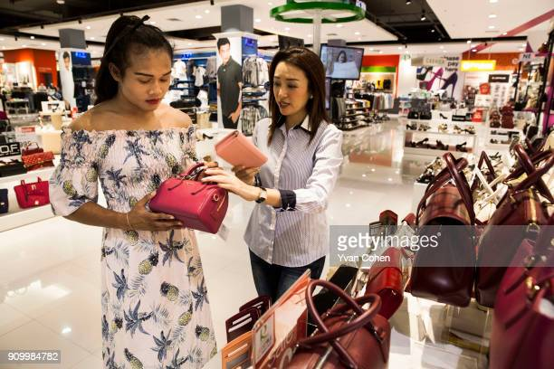 Thai transgender boxer Nong Rose browses handbags with her promoter Pariyakorn Ratanasuban at a local department store close to the Ban Charoensuk...
