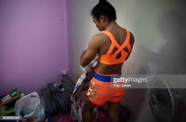 Thai transgender boxer Nong Rose changes out of her dress and into sports gear before a training routine at the Ban Charoensuk gym where she trains...