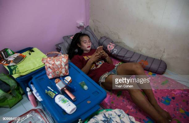 Thai transgender boxer Nong Rose takes some time out with her smart phone before a training routine at the Ban Charoensuk gym where she trains in...