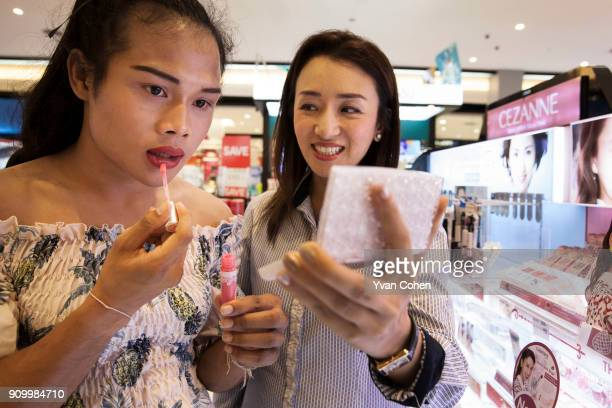 Thai transgender boxer Nong Rose tries some lipstick with her promoter Pariyakorn Ratanasuban at a local department store close to the Ban Charoensuk...