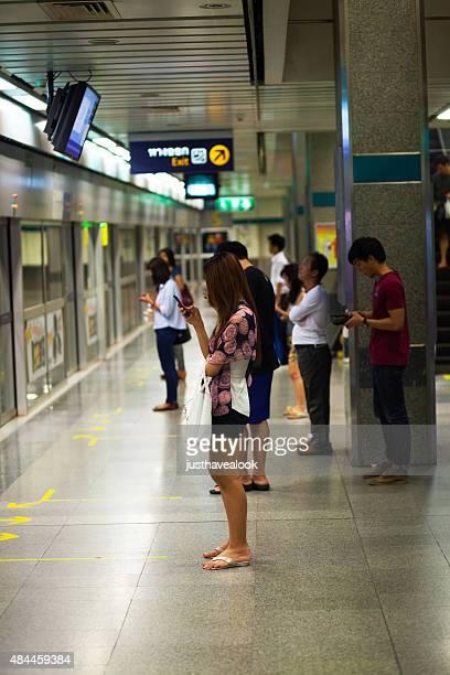 thai transexual esperando mrt y con móvil - kathoey fotografías e imágenes de stock
