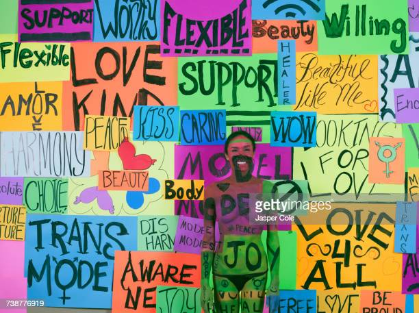 Thai transgender woman blending with message collage on wall