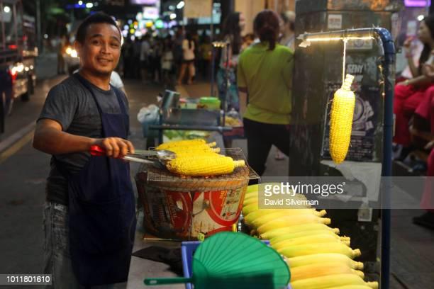 Thai vendor sells roasted corn on the popular Walking Street entertainment district on July 24 2018 in Pattaya Thailand Pattaya on Thailand's eastern...