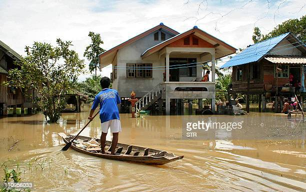 Thai villager navigates through flood water on a country boat in a partiallysubmerged village of Thailand's southern province of Phatthalung on March...
