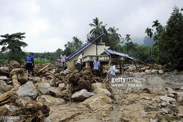 Thai villagers gather around a destroyed house at the site of a devastating mudslide at the village of Klong Heang village in Thailand's southern...
