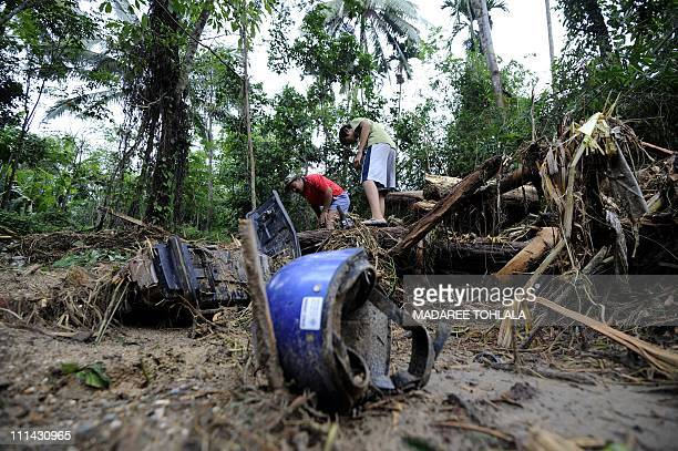 Thai villagers gather around a mudcovered motorbike at the site of a devastating mudslide at the village of Klong Heang village in Thailand's...