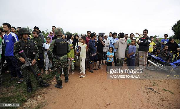 Thai villagers gather at the site where two Muslim villagers were shot dead by suspected separatist militants in Thailand's restive southern province...