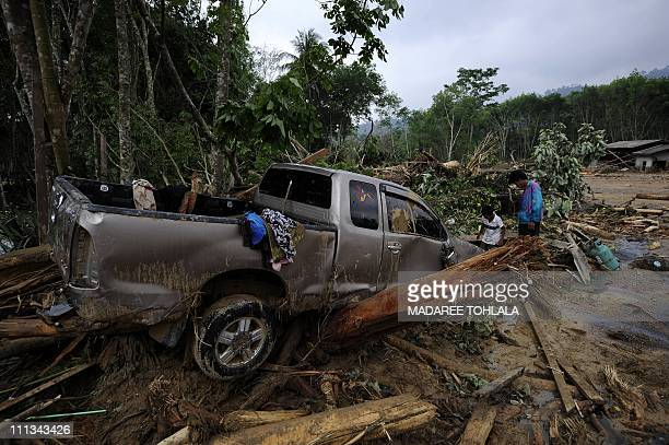 Thai villagers inspect a car which was smashed when a devastating mudslide struck the village of Nakau in Thailand's southern province of Krabi on...