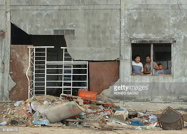 Thai villagers look out from their damage house in southern Thailand's tsunamiravaged fishing village of Nam Khem in Phang Nga province 09 January...