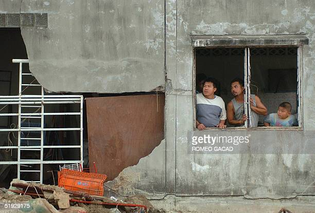 Thai villagers look out from their damage house in southern Thailand's tsunamiravagedfishing village of Nam Khem in Phang Nga province 09 January...