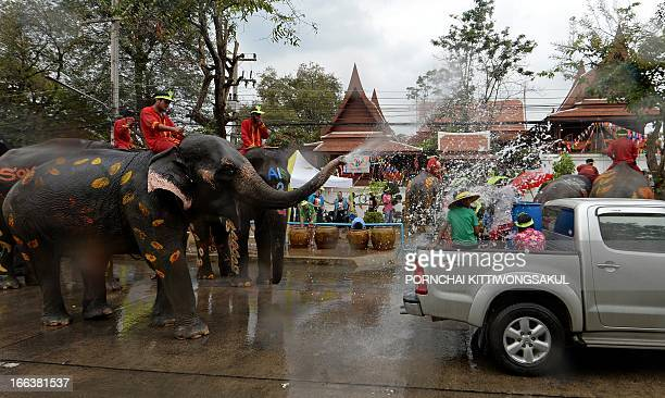 Thai villagers take part in a water battle with elephants as they join celebrations marking the Songkran Festival in Ayutthaya province on April 12...