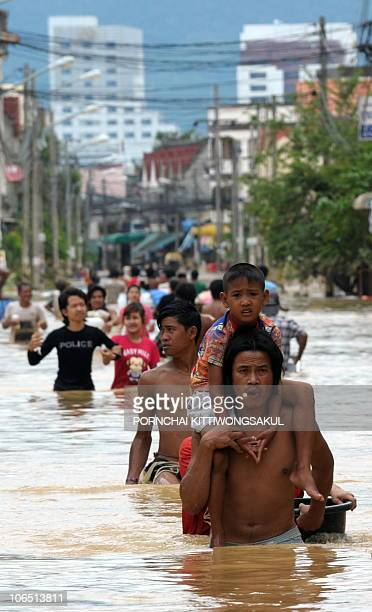 Thai villagers wade through floodwater during floods in the southern Thai city of Hat Yai on November 3 2010 Thai troops scrambled to reach thousands...