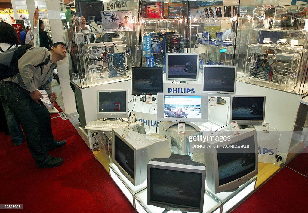 A Thai visitor looks at new computers on display at the annual computer fair in Bangkok, 20 May 2004. More than 300 computer brandname companies display their new technology to urge the computer market in Thailand. AFP PHOTO/Pornchai KITTIWONGSAKUL