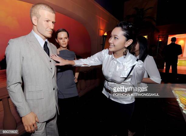 Thai visitors look at the wax model of British football player David Beckham and his wife Victoria displayed at the Louis Toussaud's Waxworks in...