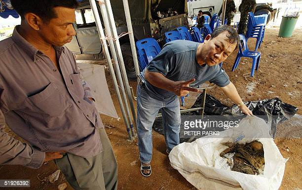Thai volunteer shows the body of a western baby who he indicates is around 2 months old at Khao Lak in Thailand's Phang Nga province 08 January 2005...