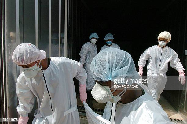 Thai volunteers carry bodies of tsunami victims from refrigirated container van at the Yan Yaw buddhist temple in Takua Pa, Phang Nga province 04...