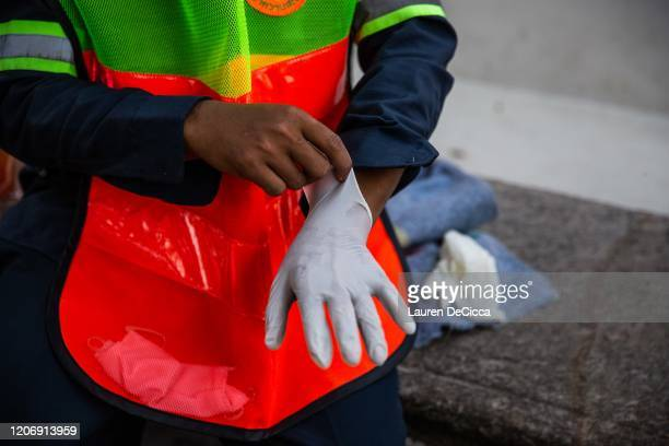 Thai volunteers put on rubber gloves as they prepare to wash and sanitize the exterior of Wat Pho on March 13, 2020 in Bangkok, Thailand. Bangkok has...