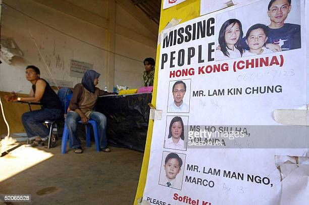 Thai volunteers sit next to a notice board with a pictures of a Chinese missing family from the sofitel resort in Khao Lak at a disaster center in...