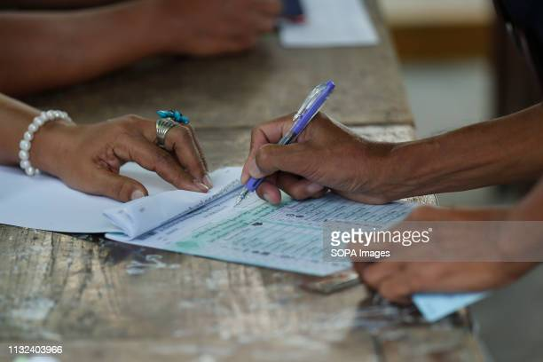 Thai voter signs her name to a ballot before casting her vote as polls opened for the Thailand election at a polling station in Bangkok