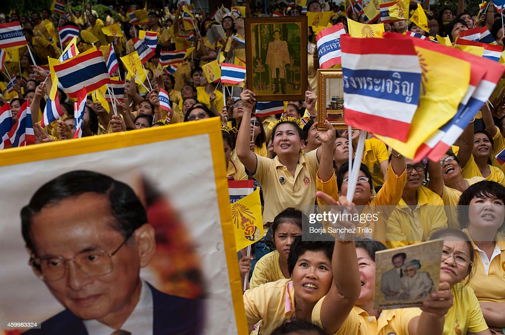 Thai well-wishers hold King Bhumibol Adulyadej portraits and try to get a glimpse of him as they gather at Siriraj Hospital on December 5, 2014 in Bangkok, Thailand. Thailand celebrates their King's 87th Birthday as King Bhumibol Adulyadej remains in the hospital where he's spent the last few months. He has cancelled his public appearance in the capital to mark the traditional celebration due to the doctors medical advice who said he wasn't well enough to attend.