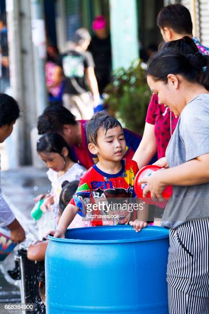 thai woman and children at barrels with water during songkran - städtische straße stock pictures, royalty-free photos & images