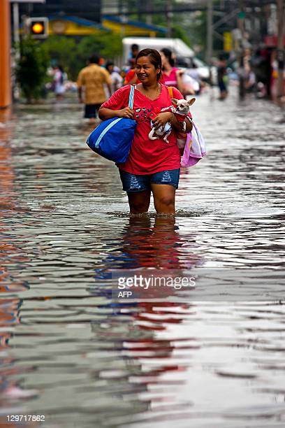 A Thai woman carries her dog through floodwaters in the inundated district of Rangsit northern Bangkok on October 20 2011 Thailand's premier warned...