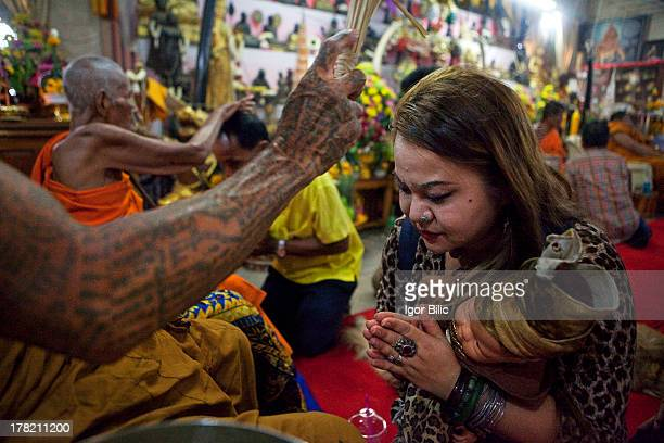 Thai woman carrying a doll, wearing matching clothes as herself, seeking blessing from a buddhist monk at Wat Bang Phra temple in Nakhon Pathom...