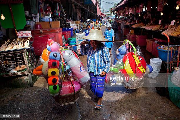 Thai woman carrying load on shoulder pole at Khlong Toey market
