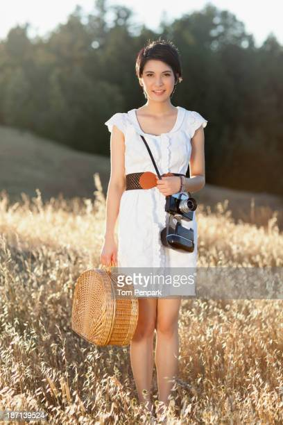 thai woman carrying picnic basket in grass - タイ人 ストックフォトと画像