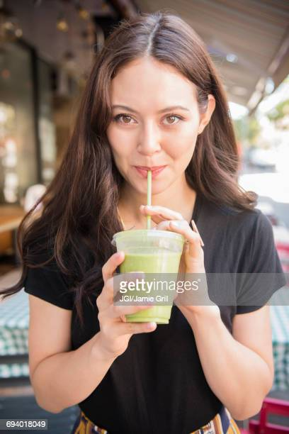thai woman drinking green smoothie - drinking straw stock pictures, royalty-free photos & images