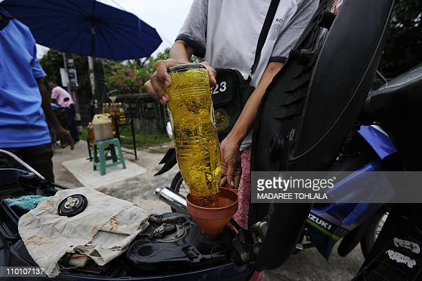 A Thai woman fills up the tank of a motorcycle at a makeshift petrol stand in Thailand's southern province of Narathiwat on March 15 2011 The price...