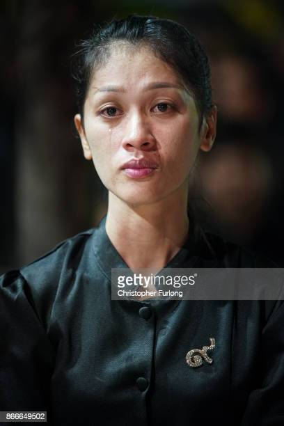 Thai woman grieves as she watches a video screen showing the funeral of the late Thai King Bhumibol Adulyadej on October 26, 2017 in Bangkok,...