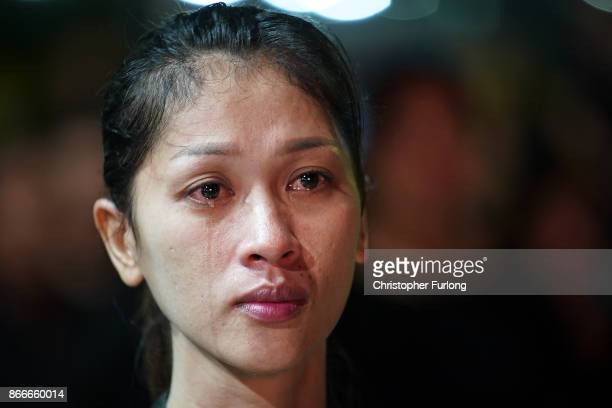 Thai woman grieves as she watches a video screen showing the funeral of the late Thai King Bhumibol Adulyadej on October 26 2017 in Bangkok Thailand...