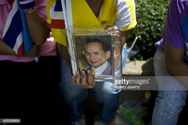 A Thai woman holds a portrait of King Bhumibol Adulyadej as she waits with others for him to arrive at the Royal Grand Palace to celebrate his 60th...