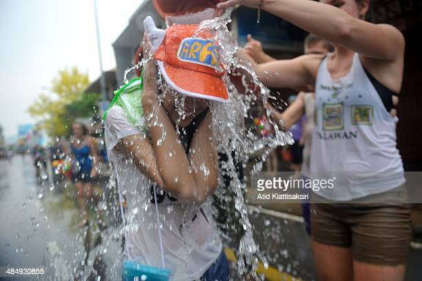 Thai woman is getting soaked by a tourist during the Songkran festival on Tapae street The Songkran festival which is the traditional Thai new year...
