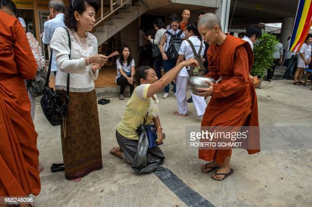 A Thai woman kneels as she donates to a newly ordained female Buddhist monk at a Buddhist temple on the outskirts of Bangkok on April 6 2017 Scissors...