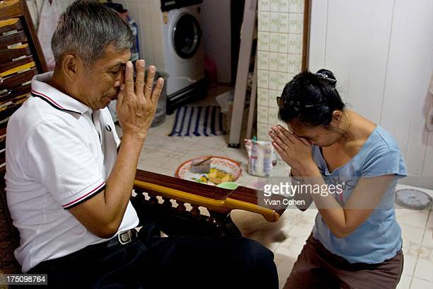 Thai woman makes a traditional 'wai' gesture of respect to her father on the day of the Thai New Year known as Songkran MODEL RELEASED