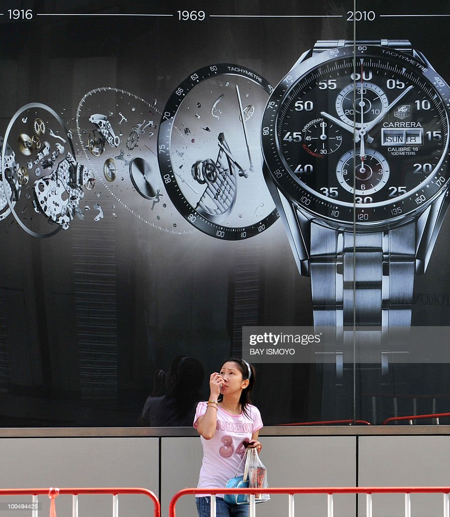A Thai woman passes an advertisement in
