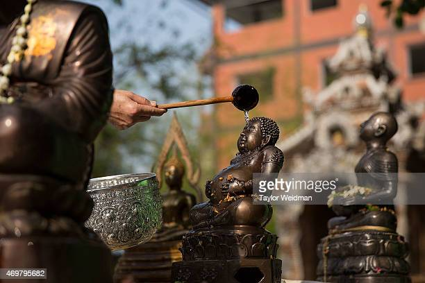 Thai woman pours an offering of scented water over a buddha image during the Songkran festival on April 15 2015 in Chiang Mai Thailand The Songkran...