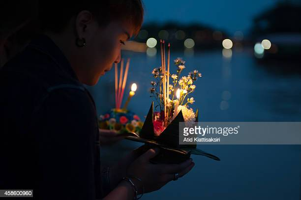 Thai woman prays before floating her krathong on the Ping river during the Loy Krathong Festival in Chiang Mai Loy Krathong is a festival celebrated...