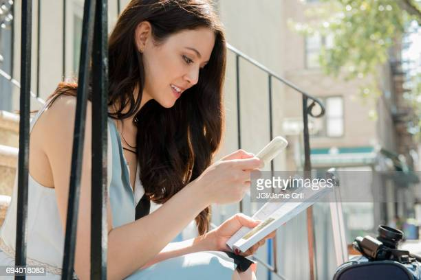 Thai woman sitting on urban staircase with cell phone and guidebook