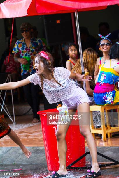 thai woman spraying water at songkran - städtische straße stock pictures, royalty-free photos & images