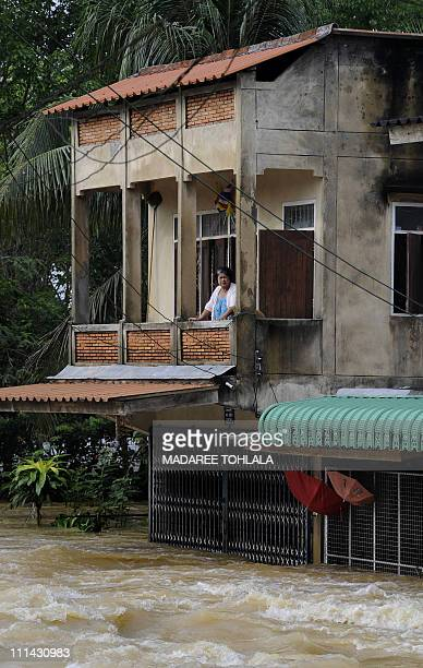 A Thai woman stands at the balcony of her flooded house following torrential rains in Thailand's southern province of Trang on April 1 2011 Severe...