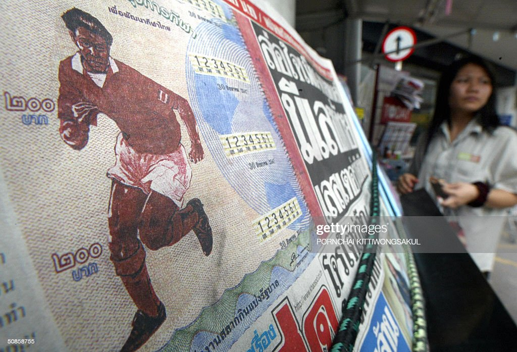 A Thai woman (R) stands next to a local newspaper showing the new lottery ticket in Bangkok, 20 May 2004. Thailand holds a public lottery to fund the purchase of a 30 percent stake in Premier League side Liverpool, as premier Thaksin Shinawatra said he was close to clinching the deal. AFP PHOTO/Pornchai KITTIWONGSAKUL