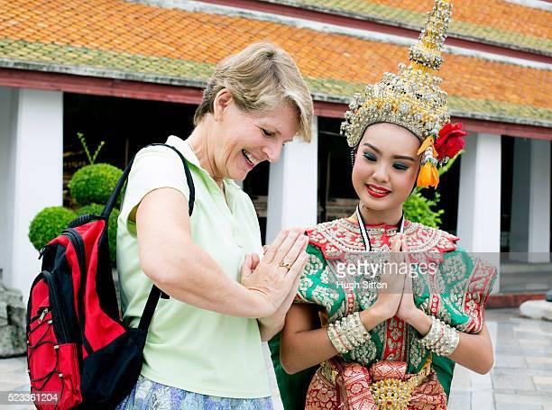 thai woman teaching tourist traditional gesture, bangkok, thailand - hugh sitton - fotografias e filmes do acervo